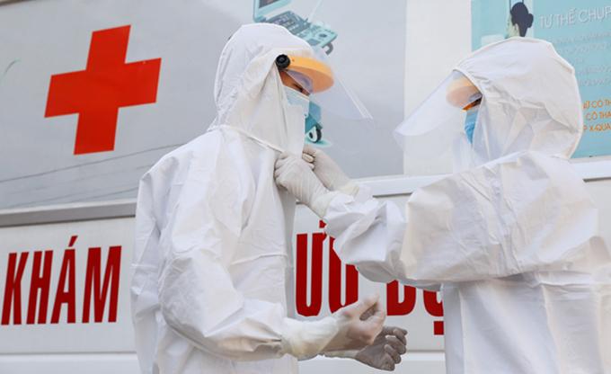 Đội ngũ y bác sĩ trên xe cứu thương, xe vận chuyển người nghi nhiễm virus corona trong trang phục bảo hộ. Ảnh: Như Quỳnh..