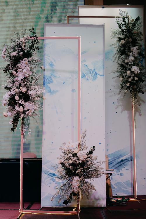 Bên cạnh sân khấu là các khung kim loại, tấm backdrop vân đá hài hòa với concept tiệc.