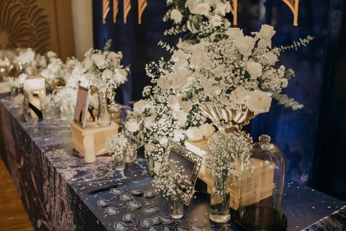 Các loài hoa được sử dụng ở tiệc cưới gồm thạch thảo, cát tường trắng, hoa bi, lan hồ điệp, hồng trắng.