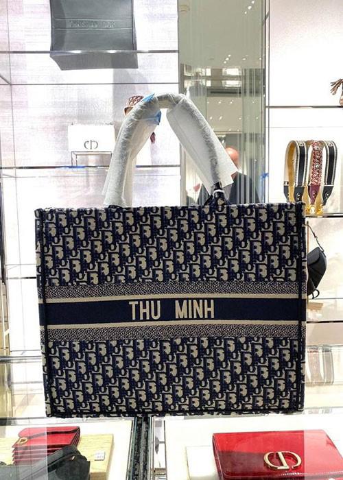 Ông xã đại gia của ca sĩ Thu Minh thể hiện độ chịu chơi khi tặng cho vợ túi Dior book tote thêu tên cô. Biên phản phổ thông của thiết kế này đã có giá từ2.650 USD đến 3.700 USD.