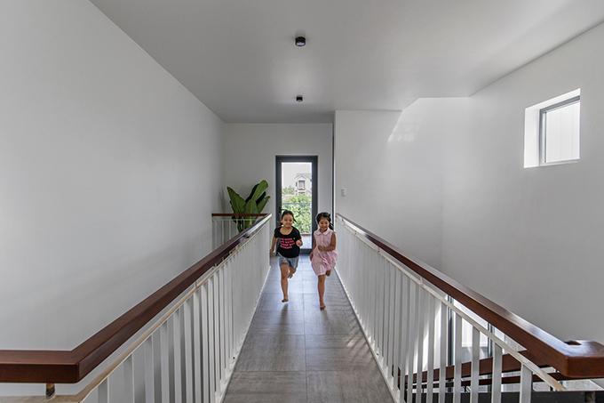 Hành lang hẹp bên trong căn nhà mở ra các không gian theo trục dọc và ngang, kết nối các phòng ngủ, khu vực chức năng khác nhau.