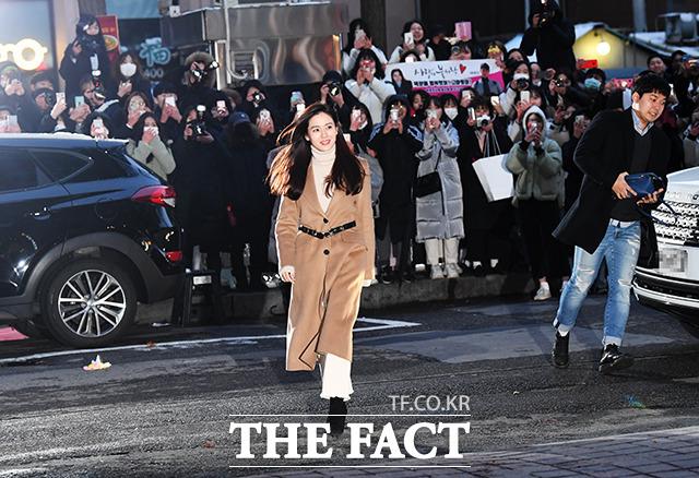 Tình đầu quốc dân của màn ảnh Hàn Son Ye Jin xuất hiện với áo cổ lọ và áo măng tô dài - một trong những kiểu trang phục quen thuộc của cô trong phim. Dưới thời tiết giá lạnh của Seoul, đông đảo người hâm mộ có mặt từ sớm để chào đón dàn diễn viên họ yêu mến.