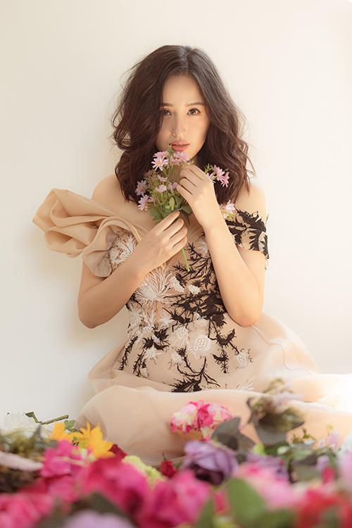 Trên nền chất liệu vải nude nhà thiết kế sử dụng chỉ trắng để mang tới hình ảnh hoa cúc lãng mạn, uyển chuyển dọc thân váy.
