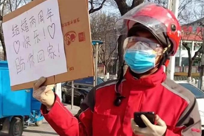 Shipper Zhang nâng tấm biển gửi tới vợ y tá ở một bệnh viện tại tỉnh Thiểm Tây nhân kỷ niệm hai năm ngày cưới. Ảnh: SCMP.