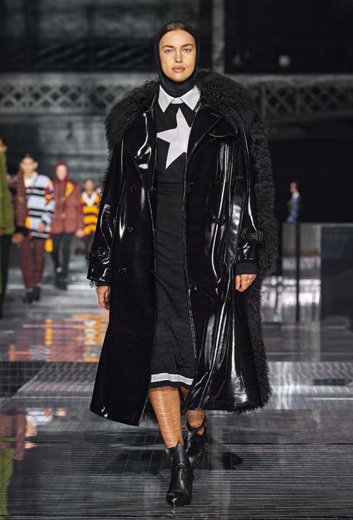 Không khoe hình thể như ở nhiều show khác, lần này Irina Shayk trình diễn set đồ đen kín cổng cao tường, phối nhiều lớp với chất liệu đa dạng, từ vải thô, nỉ, len tới da và lông nhân tạo. Bà mẹ một con giữ gương mặt nghiêm nghị, phong thái lạnh lùng như thường thấy.