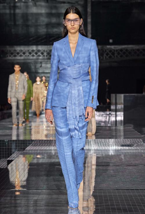 Bộ suit màu xanh nước biển trở nên độc đáo hơn khi được quấn khăn quanh eo làm điểm nhấn.