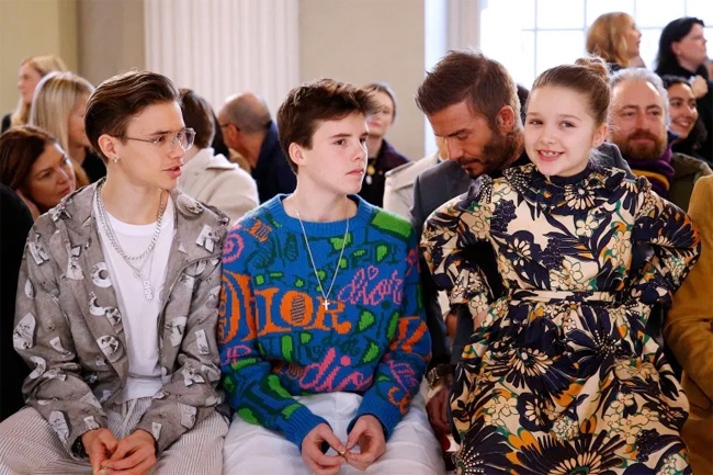 Trong khi bố và hai anh trai đều diện trang phục của nhà mốt Dior, cô nhóc Harper xinh xắn trong bộ váy hoa do chính mẹ Vic thiết kế.