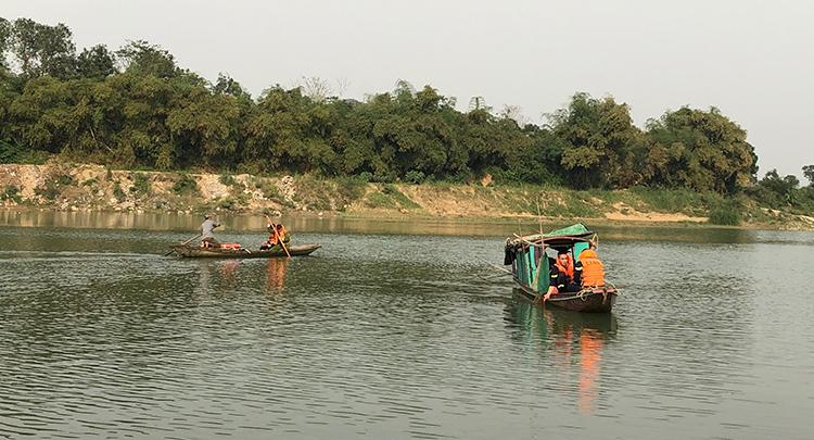 Lực lượng cứu hộ chèo thuyền tìm kiếm thi thể.