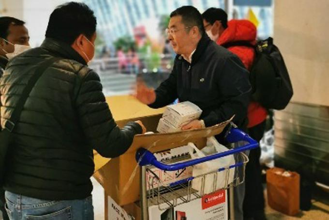 Doanh nhân Lu Yong (phải) đẩy thùng khẩu trang tại sân bay Côn Minh, Liêu Ninh, Trung Quốc. Ảnh: China Daily.
