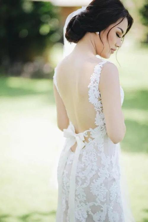 Điểm nhấn đặc sắc của thiết kế nằm ở phần lưng có khoảng hở lớn, được làm điệu bởi chi tiết nơ và họa tiết hoa ren mềm mại.
