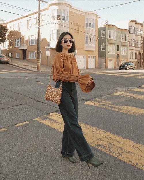 Áo blouse tay loe tông nâu trầm ấm có thể kết hợp cùng các mẫu quần tây ống đứng hoặc jeans cổ điển ống suông.