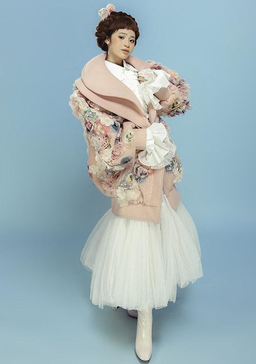 Bảo Hà diện áo khoác hồng đính hoa nổi kết hợp váy voan điệu đà. Trang phục này phù hợp mặc trong thời tiết mùa xuân vẫn còn se lạnh.