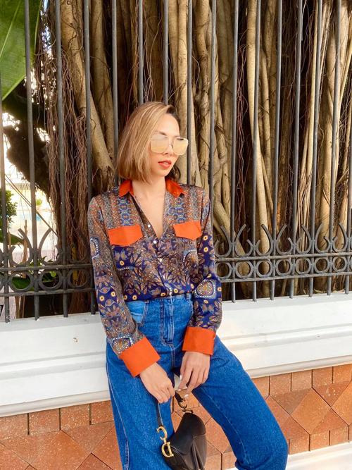 Sơ mi hoạ tiết thêm điểm nhấn bởi tông cam đào hot trend được Minh Triệu mix cùng quần jeans lưng cao kiểu cổ điển.