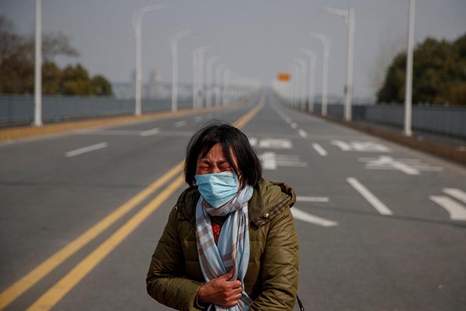 Một người mẹ ở Hồ Bắc khóc cầu xin cho con gái rời tỉnh để điều trị ung thư máu hồi cuối tháng 1. Ảnh: Reuters.