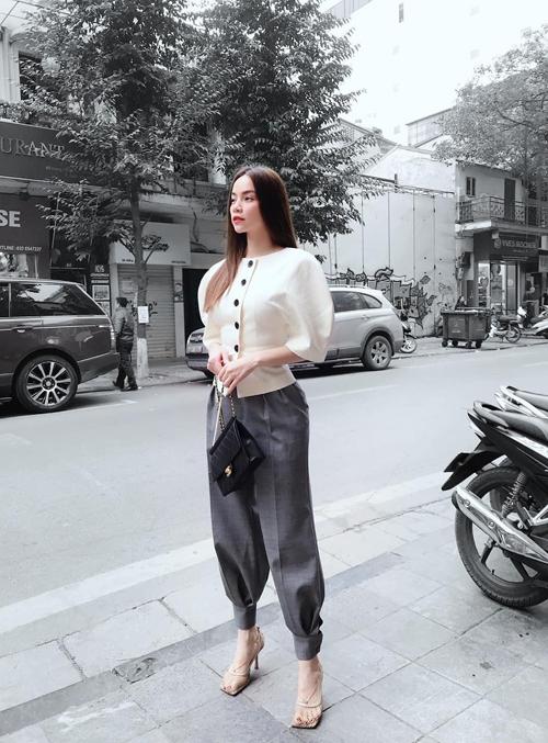 Áo tổ kén tông trắng kem được Hồ Ngọc Hà phối hợp cùng quần âu bó gấu đúng trend 2020. Phụ kiện đi kèm là giày lưới cao gót hợp mốt và túi Chanel tông đen.