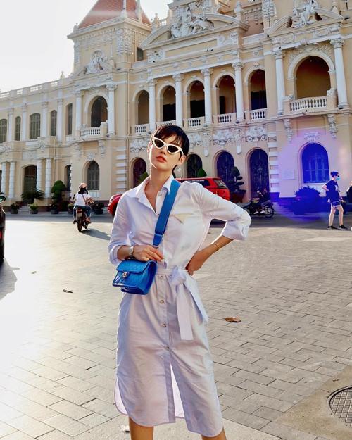 Váy sơ mi trang trí đai vải để nhấn eo mang tới sự thoải mái và tự do trong những ngày nắng. Khánh Linh chọn thêm túi Chanel tông màu thời thượng để hoàn thiện set đồ dạo phố.