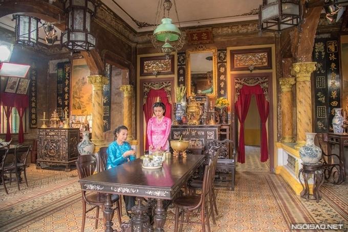 Bà hội đồng NSƯT Diệu Đức và mợ Hai Sách Cao Thái Hà trongphòng khách. Bàn ghế, tủ gỗ, rèm nhung đỏ, đèn chùm ngọc xanh, bình gốm và nhiều đồ nội thất, trang trí khác tạo nên không gian đậm chất Nam Bộ thập niên 1940.