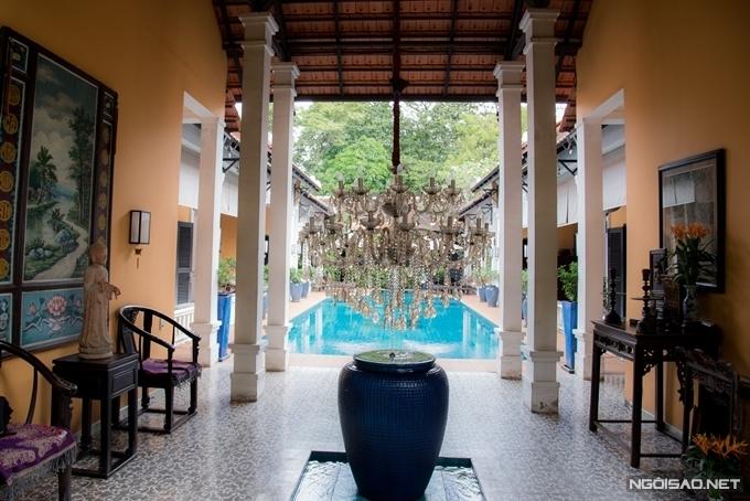 Trong nhà treo tranh cổ, bày nội thất gỗ, có hành lang hẹp dọc hai bên bể bơi.