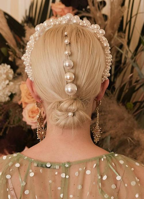 Nhà tạo mẫu khéo léo đính thêm các hạt ngọc phía sau mái tóc, giúp cô dâu có diện mạo nổi bật ở mọi góc nhìn.