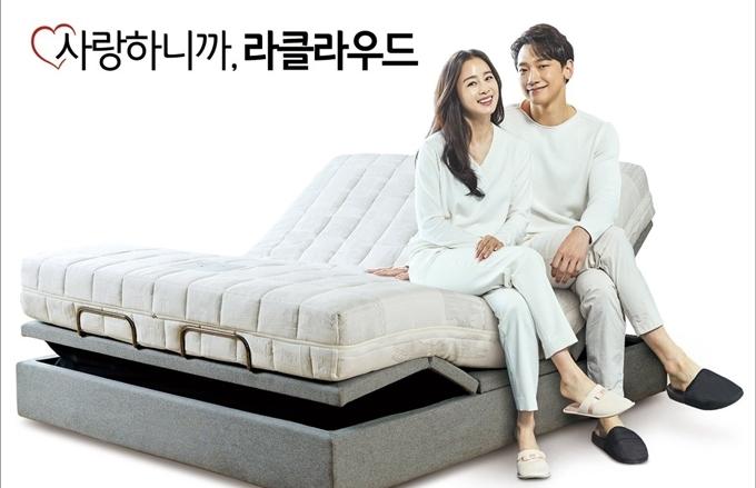 Cặp vợ chồng ngôi sao chụp hình quảng cáo sản phẩm giường ngủ.