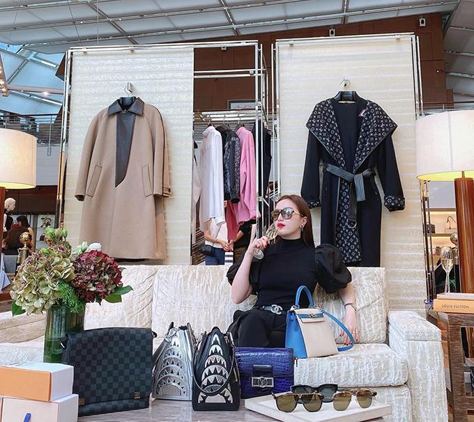 Nữ ca sĩ thảnh thơi uống rượu vang khi mua sắm tại cửa hàng sang trọng của Louis Vuitton tại Singapore.