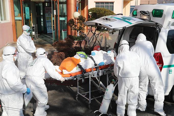Nhân viên y tế chuyển bệnh nhân nhiễm Covid-19 lênxe cứu thương tại thành phố Daege, Hàn Quốc hôm 23/2. Ảnh: AFP.