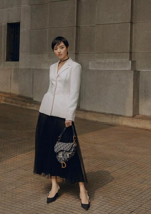 Khánh Linh với hình ảnh thanh lịch và sang chảnh khi diện nguyên set đồ đến từ thương hiệu Dior. Tông trắng đen được fashionista mix-match hoàn hảo từ kiểu áo tôn đường công, chân váy và giày cao gót mũi nhọn, túi yên ngựa.