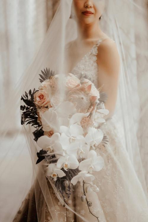 Jenny chọn hoa cưới dáng dài kết từ hồng, lan hồ điệp trắng thay vì hoa bó tròn, mang đến sự cổ điển cho hôn lễ.