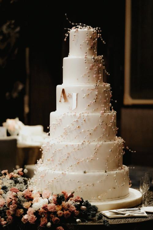 Bánh cưới của uyên ương mang tông trắng, được điểm chữ A - J, ký tự trong têncủa cô dâu, chú rể. Thân bánh được điểm hạt đường tạo hình giống hạt ngọc trai.