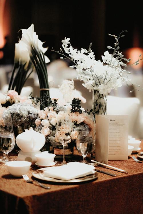 Bàn tiệc được tô điểm với những bình hoa tươi mang sắc trắng. Không gian tiệc ấm cúng với khăn trải bàn màu nâu.