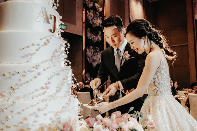 Cô dâu chú rể cùng cắt bánh kem để đãikhách mời.