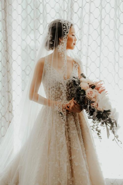 Trong ngày trọng đại, cô dâu Jenny diện váy cưới họa tiết ren hoa nhí, dáng A xòe nhẹ. Khăn voan dài ren hoa giúp cô dâu hoàn thiện vẻ ngoài nữ tính.
