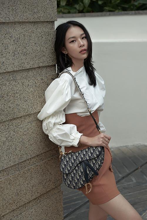 Mẫu Saddle Bag của Dior được Phí Phương Anh chọn làm điểm nhấn cho bộ cánh gam màu thanh nhã mix cùng váy sắctrung tính.