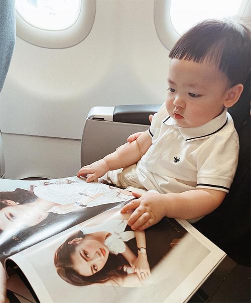 Lần đầu tiên đi du lịch, Kem rất thích thú khi được xem ảnh mẹ trong cuốn tạp chí trên máy bay.