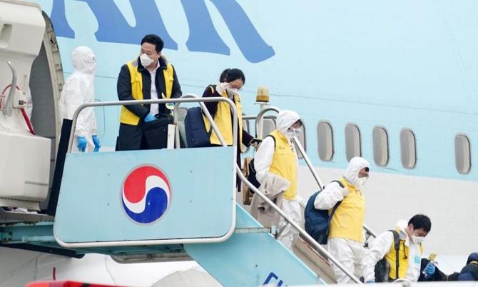 Các quan chức Hàn Quốc mặc đồ bảo hộ trên chuyến bay của Korean Air được điều đến Vũ Hán sơ tán công dân hồi tháng 1. Ảnh: AFP.
