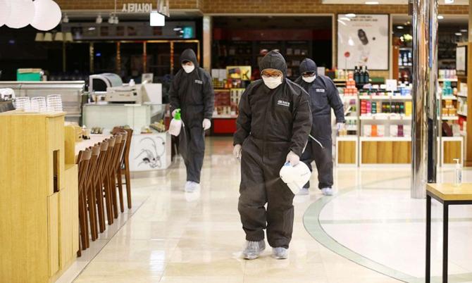 Các nhân viên y tế phun khử trùng một trung tâm thương mại ở Deagu, Hàn Quốc. Ảnh: AFP.