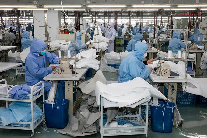 Các công nhân mặc đồ bảo hộ làm việc trong một nhà máy ở Quảng Đông, Trung Quốc. Ảnh: NYT.