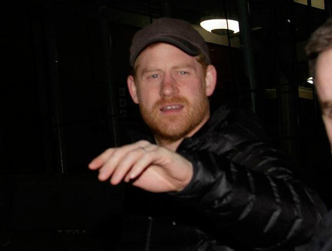 Công tước xứ Sussex đội chiếc mũ lưỡi trai quen thuộc khi về Anh tối 25/2. Ảnh: Splashnews.