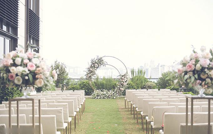 Uyên ương chọn cổng cưới tròn, được tô điểm bởi hoa hồng với mong ước tình yêu giống như vòng tròn, mãi tuần hoàn, không có điểm dừng. Cặp vợ chồng chọn ghế gỗ bọc đệm trắng cho không gian làm lễ ngoài trời.