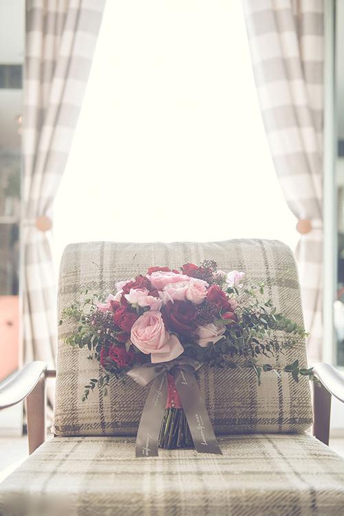 Bó hoa cầm tay được kết dạng tròn, mang sắc hồng, đỏ đến từ những bông hoa hồng.
