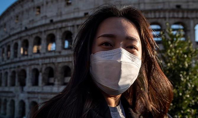 Du khách bịt kín khẩu trang khi du lịch Roma, Italy. Ảnh: Forbes.