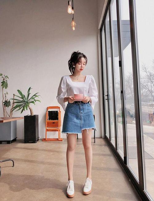 Chân váy jeans rách với phần vạt bất đối xứng khiến set đồ street style ngày cuối tuần trở nên phá cách và bắt mắt hơn.