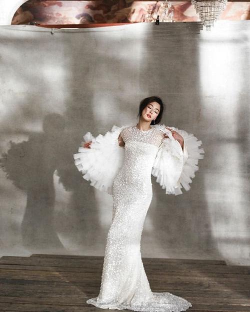 Váy cưới đính ngọc trai giúp cô trở nên nổi bật trong tấm hình. Ngoài ra, người đẹp còn diện thêm áo choàng từ vải tulle.