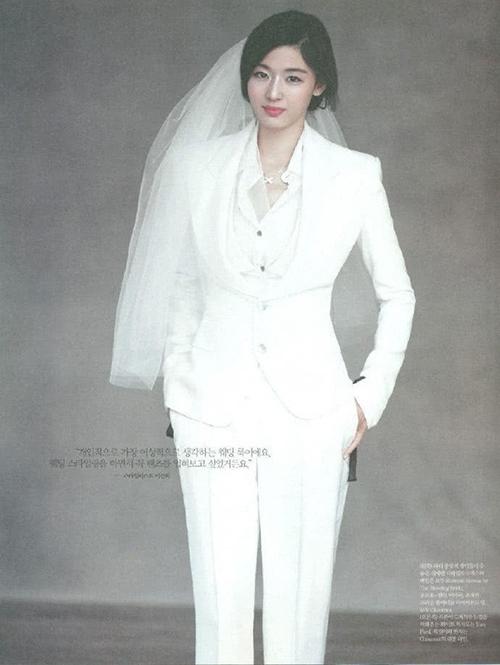 Mẫu suit trắng là lựa chọn dành cho cô dâu cá tính trong ngày đại hỷ. Người đẹp sử dụng phụ kiện là khăn voan ngắn không hoạ tiết.