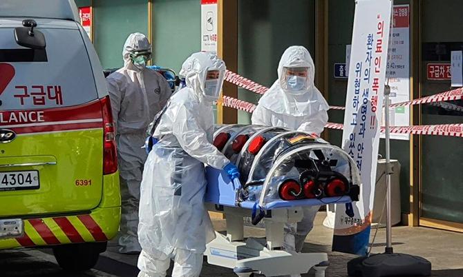 Các nhân viên y tế Hàn Quốc đưa bệnh nhân nhiễm Covid-19 vào viện. Ảnh: Yonhap.