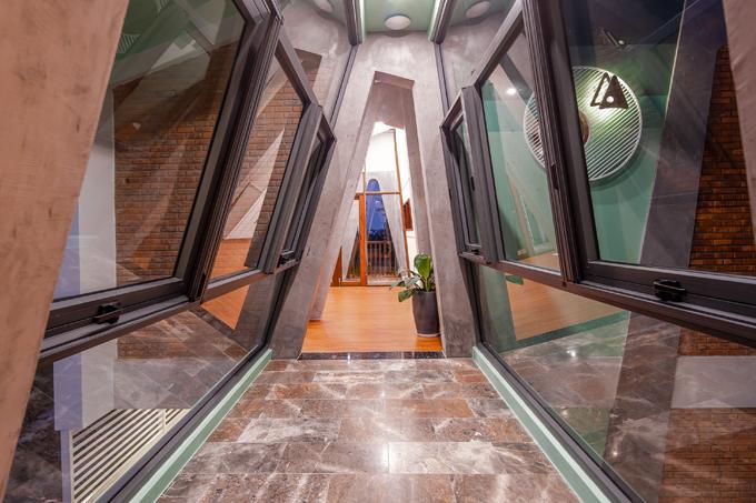 Hành lang giữa các phòng của khối nhà có vách kính, mang dáng vẻ hiện đại thay vì vách tường bê tông truyền thống.