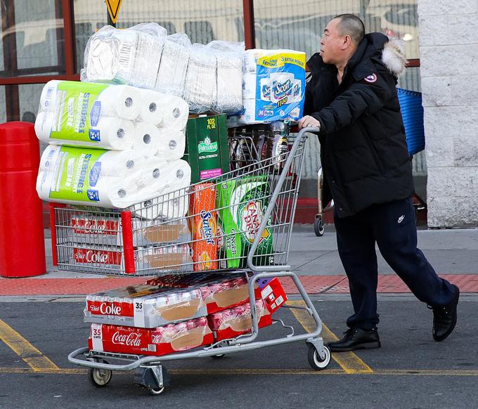 [Caption]Những chiếc xe chở hàng trong siêu thị được người mua sắm chất đầy giấy vệ sinh, nước đóng chai và thực phẩm đóng hộp.