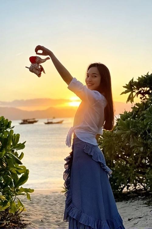 Người đẹp tìm thấy giây phút bình yên dưới ánh hoàng hôn bên một bờ biển.