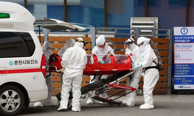 Các nhân viên y tế đưa một bệnh nhân nhiễm Covid-19 đến bệnh viện. Ảnh: Korea Times.