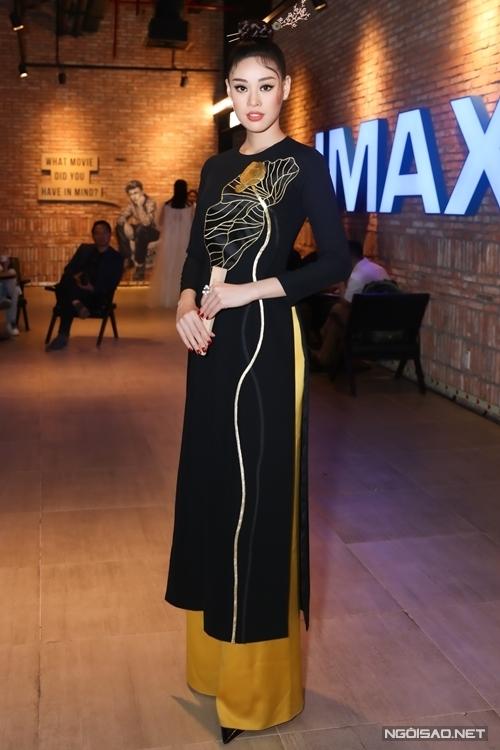 Khánh Vân diện áo dài họa tiết hoa sen, vấn tóc cao và cài trâm, cầm quạt khi dự sự kiện.